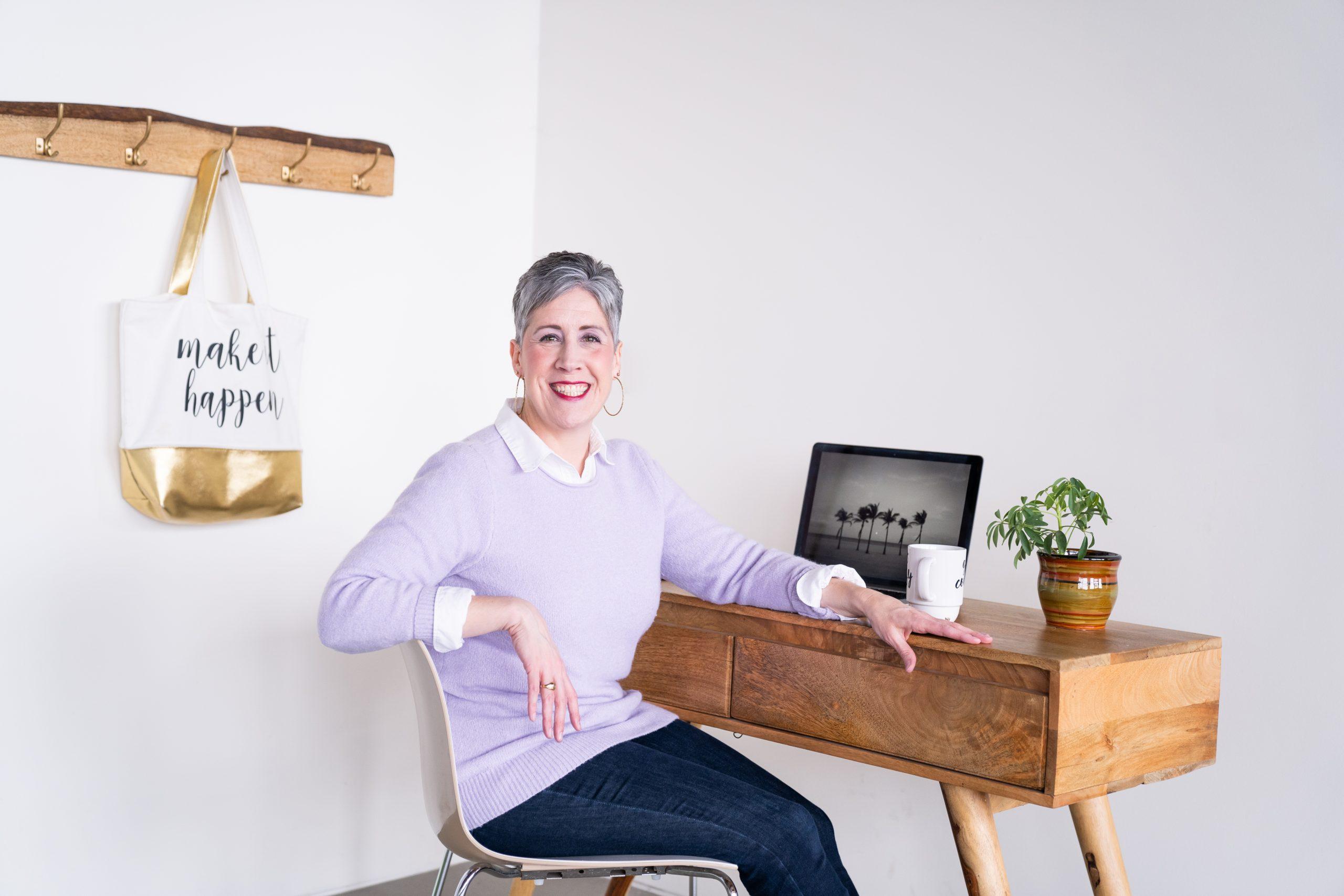 Woman in purple sweater sitting at work desk